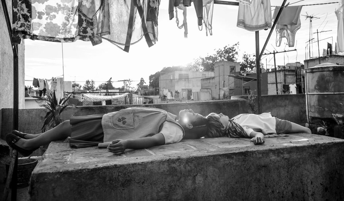Roma Cleo and one of the children lie down on the roof