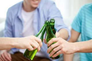 People clinking beer bottles at home.