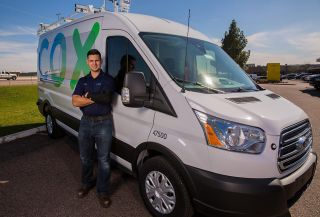 Cox technician in front of service truck