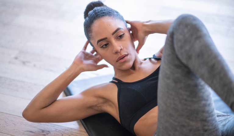 Woman doing a side crunch as part of an abs workout