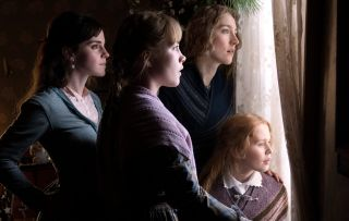 Four women staring out of a window