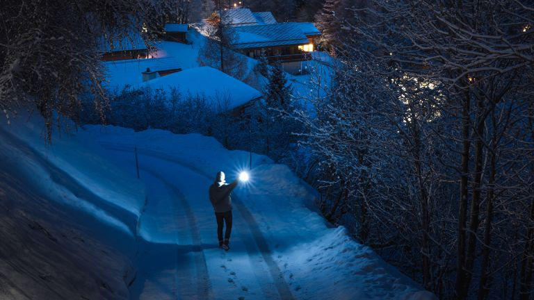 Best torch / flashlight: man walking down snowy path with a torch