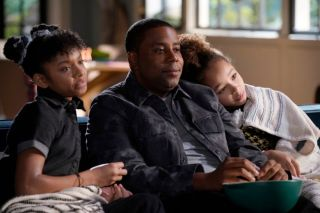 Kenan and his daughters watch tv together in the show 'Kenan.'