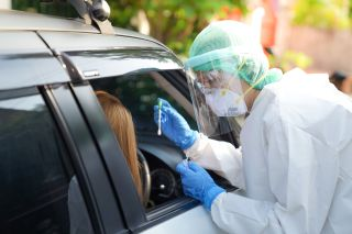 A health care professional conducting a COVID-19 test at a drive through testing site.
