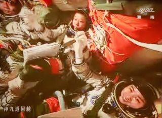 Shenhzhou 9 astronauts celebrate manual docking with Tiangong 1 space lab.