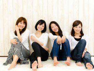 Four Asian women smiling.
