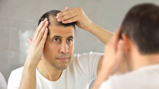 A man checks out his receding hairline in the mirror.