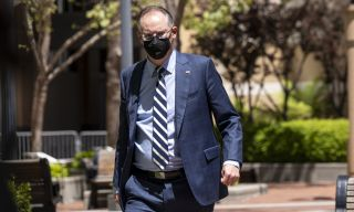Tim Sweeney wearing a suit and cloth facemask, walking outside the US district courthouse in Oakland on the first day of the Epic v Apple trial.