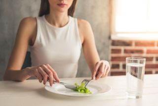 Cropped image of a woman eating a single piece of broccoli with a glass of water next to her plate.