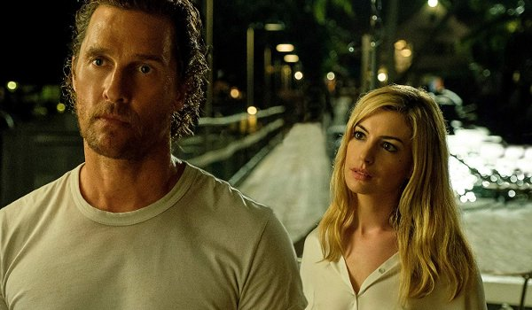 Serenity Anne Hathaway stands behind Matthew McConaughey, trying to lure him in