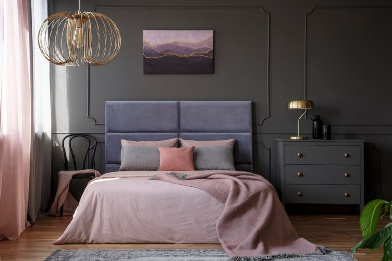 dramatic bedroom with velvet headboard and blush pink bedding