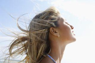 A woman tilts her face toward the sun.
