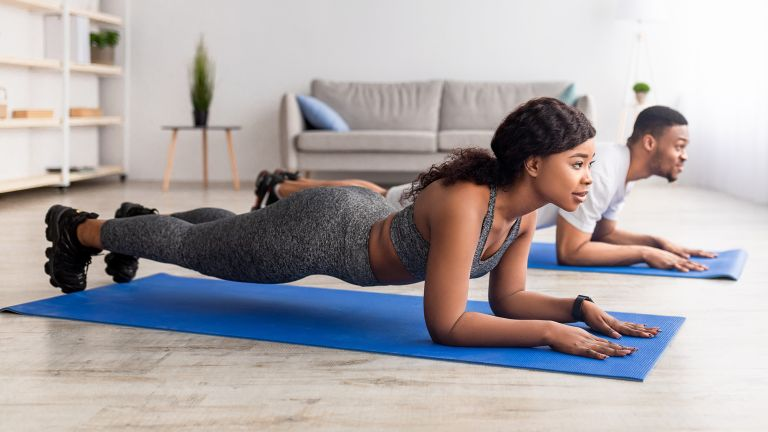 Man and woman doing planks as part of a Pilates workout