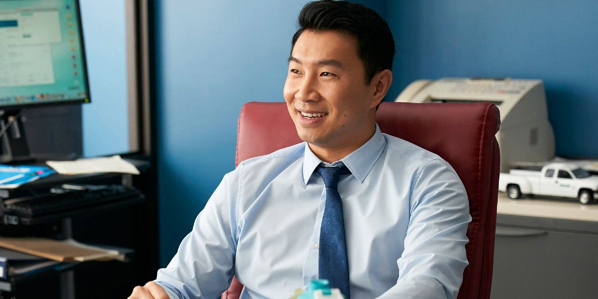 Simu Liu smiles while sitting at his desk in Kim's Convenience
