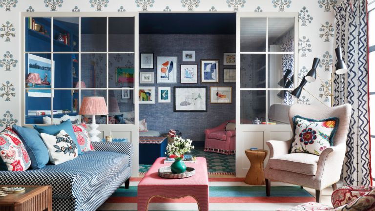 An example of broken plan living room ideas showing a blue sofa opposite a cream armchair with bright cushions in front of glass dividing doors