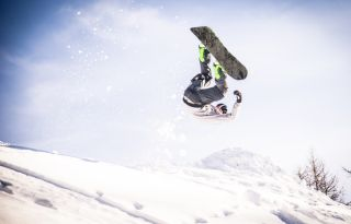 Snowboarder doing a trick in the snow.