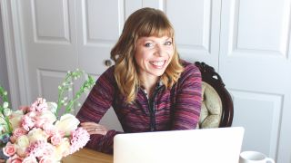 An image of UX expert Sophia V Prater – she's sat at a desk and smiling.