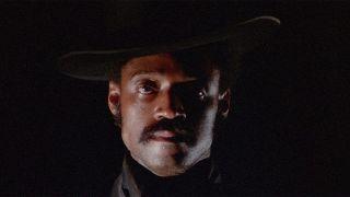 Melvin Van Peebles standing in front of a black background in Sweet Sweetback's Baadasssss Song.