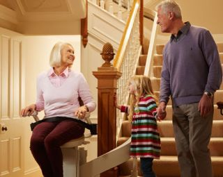 Grandma on Stair lift with grandpa and grandchild on stairs