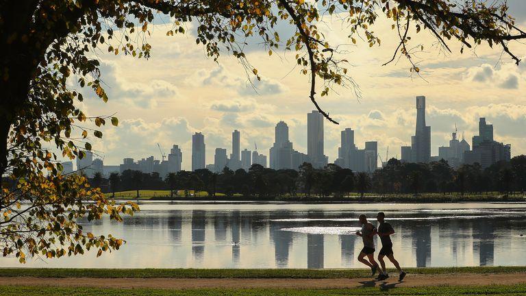 Two people running through an urban park