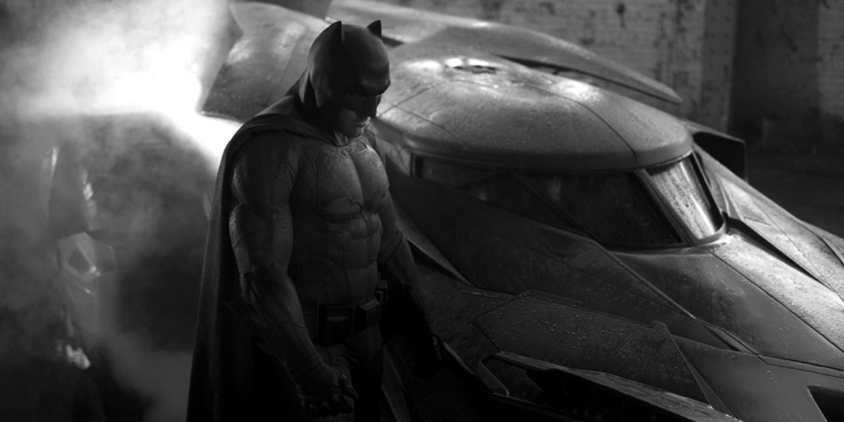 Batman looking dour next to the batmobile
