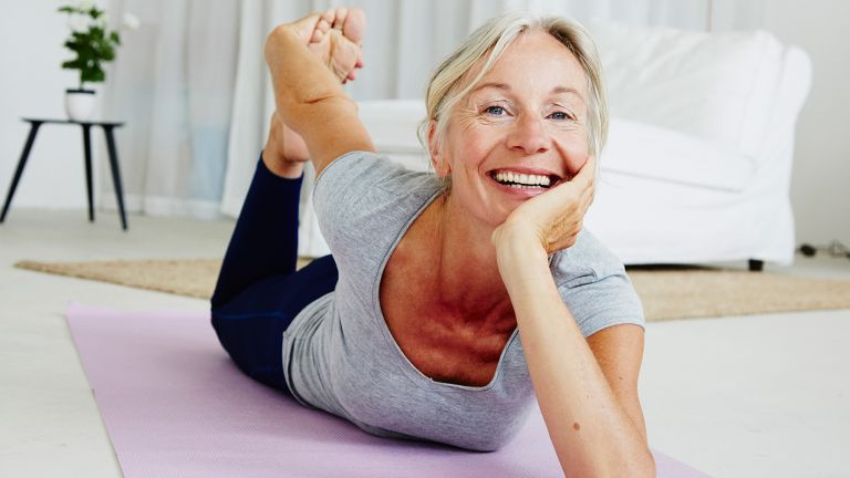 An older woman demonstrates her flexibility by grabbing her foot from behind