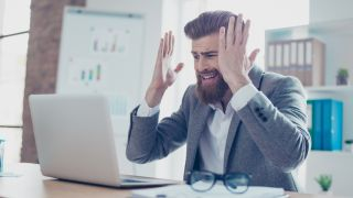 Stressed out businessman looking at laptop