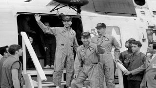 The crewmembers of the Apollo 13 mission step aboard the USS Iwo Jima, after splashdown and recovery operations in the South Pacific Ocean on April 17, 1970. Exiting the helicopter from left to right are Fred Haise, James Lovell and John Swigert.