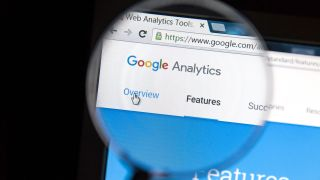 Someone looking at Google Analytics through a magnifying glass
