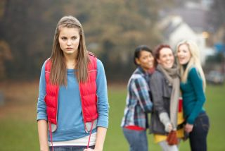 upset teen girl with other girls gossiping in the background