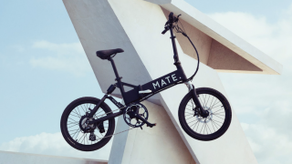 Mate Icon e-bike shown against an abstract geometric background
