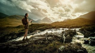 A woman walks across an impressive landscape