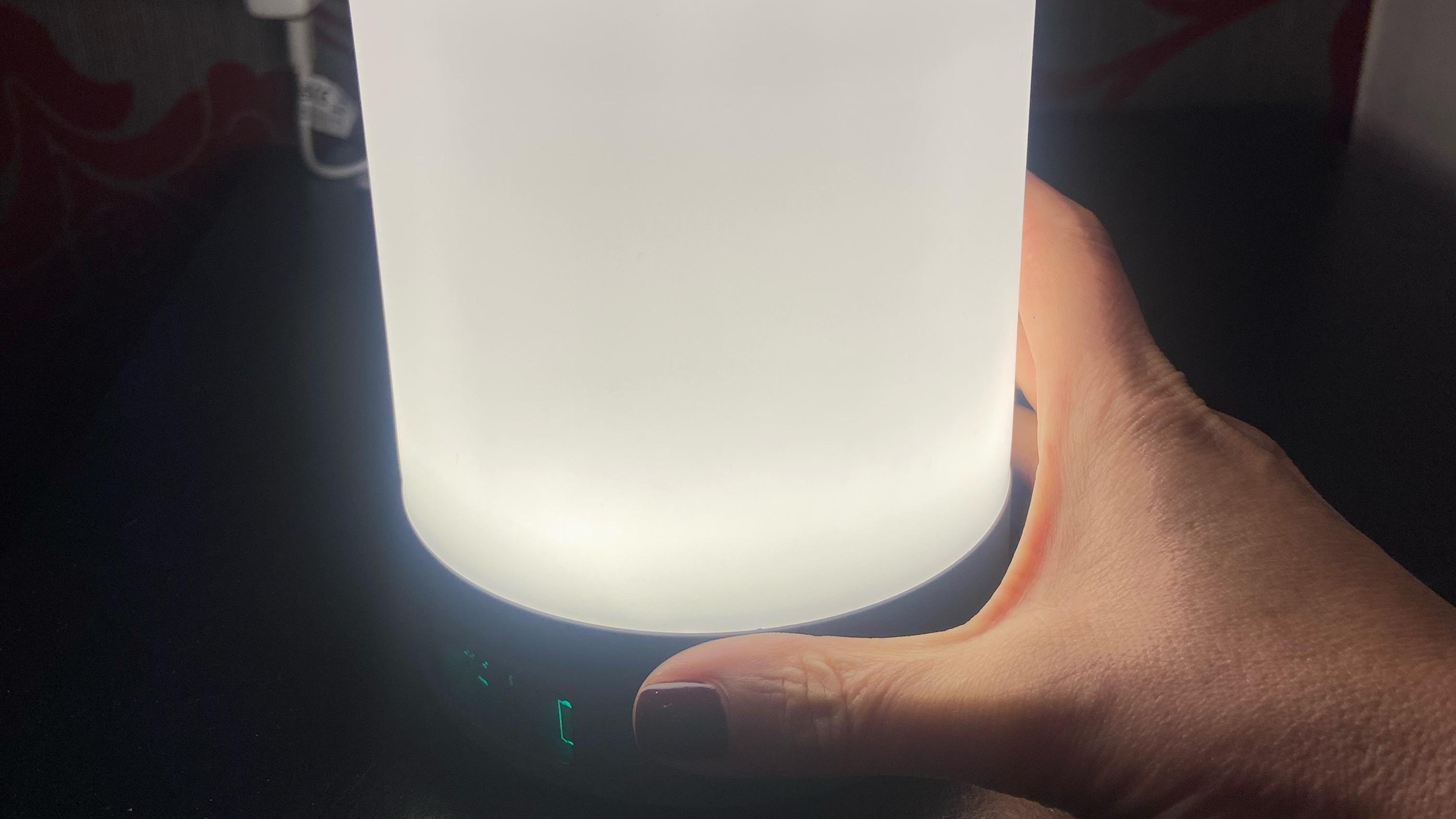 Woman's hand holding Beurer Wake Up Light WL50, emitting white light