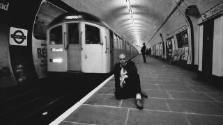 Peter Gabriel, British singer-songwriter and musician, poses shaven head sitting on a platform at Chancery Lane underground station in London