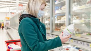 Woman wearing a face mask, looking down at a frozen food product in her hand. She's in the frozen food section of a grocery store