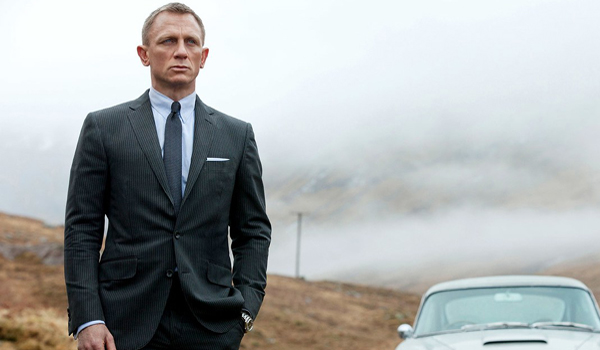 Skyfall Daniel Craig in a suit as James Bond next to car