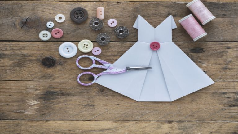 Paper sewing: Small paper dress on table amongst sewing equipment