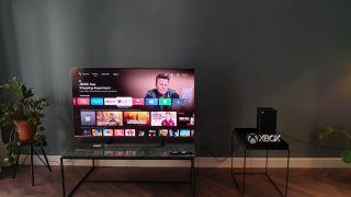 Das neue Modell von TCL im Wohnzimmer neben einer Xbox