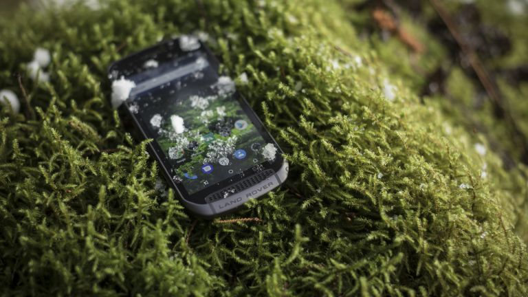 The Land Rover Explore smartphone covered in ice, on moss