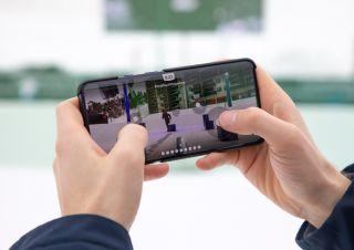 Käyttäjä ohjaa lumipallorobottia OnePlus-puhelimellaan.