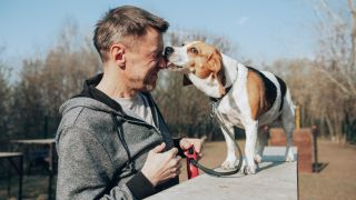 A man with a beagle licking his nose. Humans have two nostrils, but most people have one that is dominant.