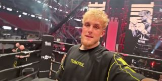 Jake Paul holding a camera inside a boxing ring with a Team Paul shirt on before his fight with Ben Askren.