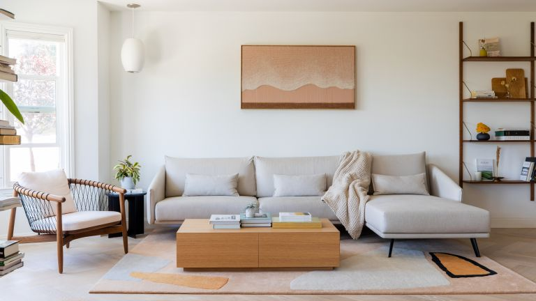 A white living room with taupe sofa, oak box coffee table, wooden framed armchair and large bay windows