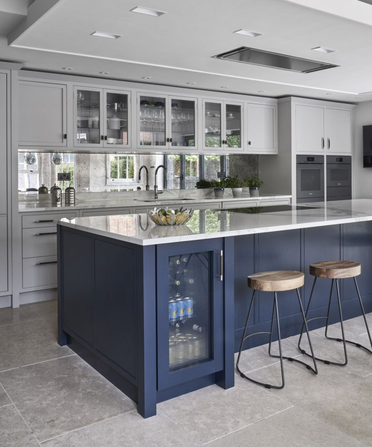 Kitchen cupboard storage ideas in a kitchen with a large blue island, with features including a drinks fridge and brown leather bar stools