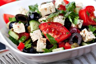 A salad with tomatoes, feta cheese and black olives