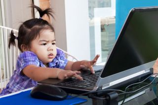 a baby types away on a laptop computer