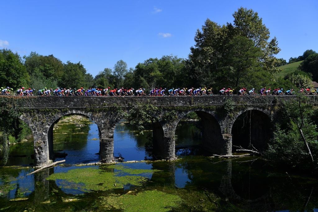 The peloton crosses a bridge early on stage 11