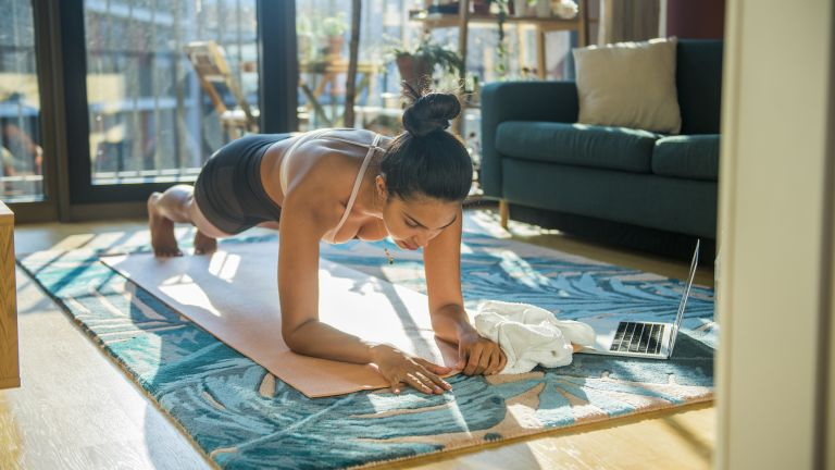 Person planking on a yoga mat in their living room