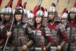 Yifei Liu (center) and Yoson An (right) as Honghui in the live-action remake of Disney's Mulan.