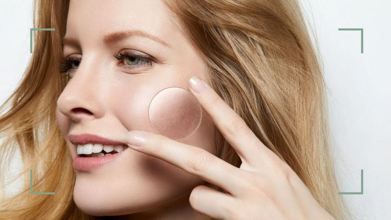 how to get rid of whiteheads main image of woman holding a magnifying glass to her cheek